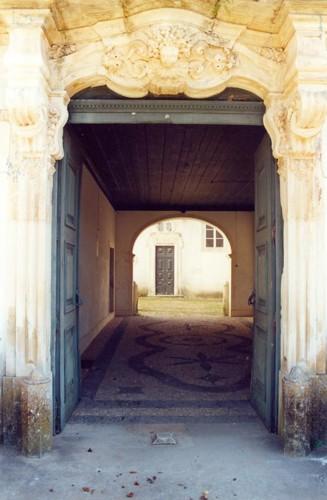 Passagem, através do portal principal, ao pátio