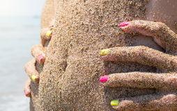 as-meninas-incham-se-coberto-com-areia-da-praia-em