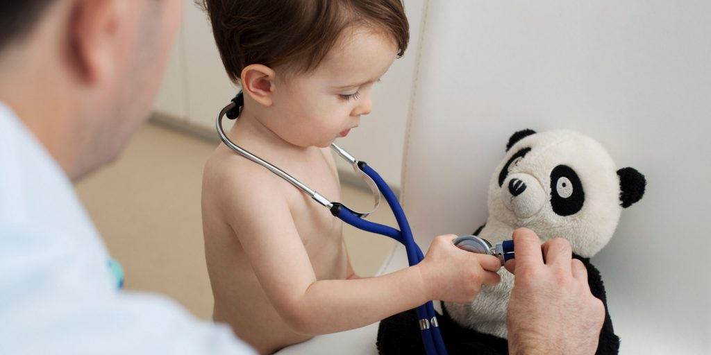 Little boy and doctor using stethoscope on panda toy